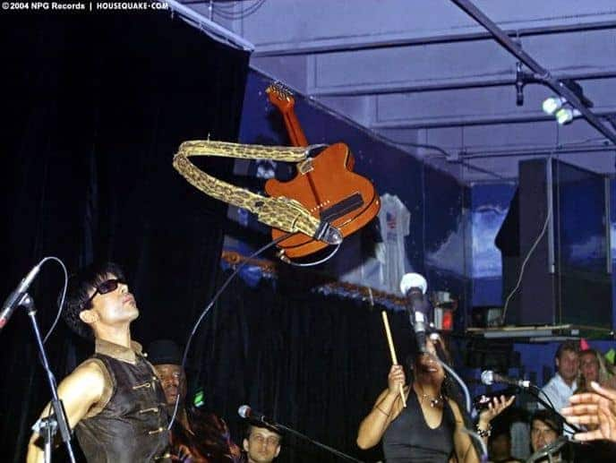 A picture of Prince with his Hohner T-style guitar in mid-air.